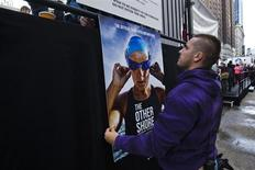 A worker holds up a poster with the image of U.S. long-distance swimmer Diana Nyad while she attends her 48 hour continuous swim at Herald Square in New York October 8, 2013. REUTERS/Eduardo Munoz