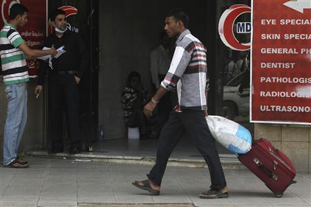 A foreign worker pulls his luggage along a street in Riyadh November 4, 2013. REUTERS/Faisal Al Nasser