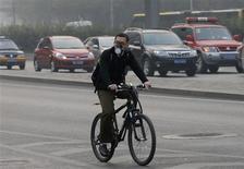 Un hombre con una mascarilla en su rostro anda en bicicleta en un día con esmog en Pekín, oct 28 2013. La capital china, aquejada por un denso smog y fuertes congestionamientos de tránsito, reducirá las cuotas de autos nuevos en la ciudad en casi un 40 por ciento el 2014, para rebajar las emisiones y los peligrosos niveles de contaminación, dijo en su página de internet el gobierno de Pekín. REUTERS/Kim Kyung-Hoon