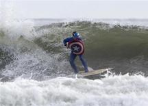 A participant dressed as Captain America surfs during the third annual Rockaway Halloween surf competition at Rockaway Beach in the Queens borough of New York November 2, 2013. REUTERS/Eric Thayer