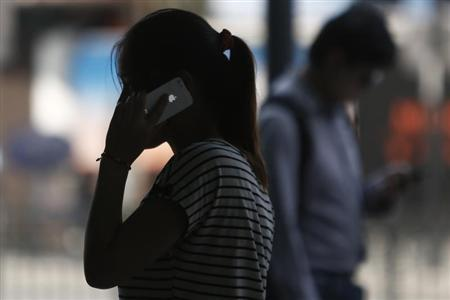 A woman speaks on her iPhone as she walks on a busy street in downtown Shanghai September 10, 2013. REUTERS/Aly Song