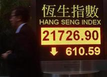 Человек проходит мимо экрана, на котором отображаются данные об индексе Hang Seng, в Гонконге 5 апреля 2013 года. Азиатские фондовые рынки, кроме Японии, снизились в среду за счет неуверенности в планах ФРС и в ожидании китайской статистики и политических решений властей Китая. REUTERS/Bobby Yip