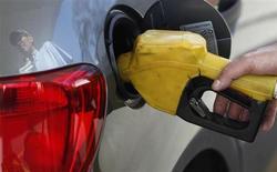 Работник АЗС заправляет автомобиль в Сан-Паулу 22 августа 2013 года. Цены на нефть Brent снизились до минимального уровня с начала июля, так как инвесторы не желают открывать новые позиции, ожидая важных новостей от Европейского центрального банка и из США. REUTERS/Paulo Whitaker