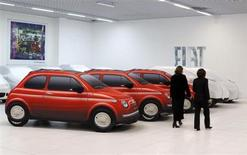 Women walk past Fiat cars under covers at a dealership in Rome October 30, 2012. REUTERS/Alessandro Bianchi