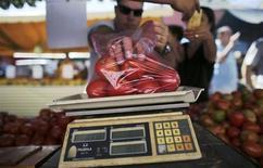 Cliente pesa tomates em feira livre no bairro da Mooca, na cidade de São Paulo. Pressionado pelos preços de alimentos, o Índice Nacional de Preços ao Consumidor Amplo (IPCA) acelerou a alta a 0,57 por cento em outubro, mas em 12 meses a inflação mostrou desaceleração, em resultados melhores do que o esperado. De acordo com o IBGE, o principal responsável pelo resultado de outubro foi o grupo Alimentação e Bebidas, com alta mensal de 1,03 por cento, após 0,14 por cento em setembro, e representando 0,25 ponto percentual no mês, ou 44 por cento do índice. 4/05/2013. REUTERS/Nacho Doce