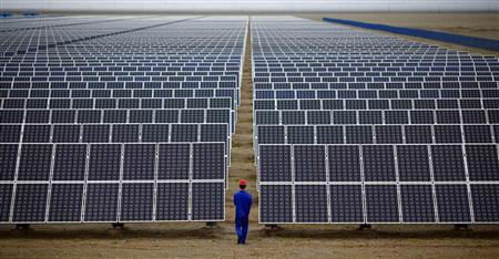 A worker inspects solar panels at a solar Dunhuang, 950km (590 miles) northwest of Lanzhou, Gansu Province in this September 16, 2013 file photo. REUTERS/Carlos Barria/Files
