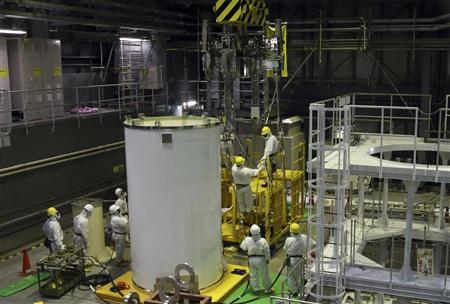 Workers wearing protective suits and masks work on a crane for a transport container inside the No. 4 reactor building at the tsunami-crippled TEPCO's Fukushima Daiichi nuclear power plant in Fukushima prefecture, November 7, 2013. REUTERS/Tomohiro Ohsumi/Pool