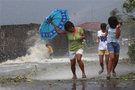 Residents walk along the coastal village while strong winds from Typhoon Haiyan battered Bayog town in Los Banos, Laguna, south of Manila November 8, 2013. REUTERS/Charlie Saceda