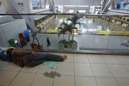 A stranded passenger lies on the floor inside Ninoy Aquino International airport in Pasay city, metro Manila November 8, 2013, after nearly 200 local flights have been suspended due to Typhoon Haiyan that hit central Philippines. REUTERS/Romeo Ranoco
