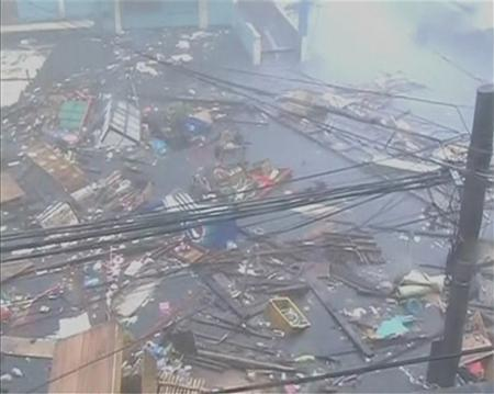 Debris float on a flooded road as strong winds and rain continue to batter buildings after Typhoon Haiyan hit Tacloban city, Leyte province in this still image from video November 8, 2013. REUTERS/ABS-CBN via Reuters TV