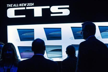 Car aficionados stand in front of a display of color options for the new 2014 Cadillac CTS sedan during an unveiling ceremony in New York, March 26, 2013. REUTERS/Lucas Jackson