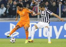 Real Madrid's Marcelo (L) is challenged by Juventus' Martin Caceres during their Champions League soccer match at Juventus stadium in Turin November 5, 2013. REUTERS/Giorgio Perottino