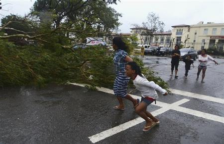 Residents rush to safety past a fallen tree during strong winds brought by Typhoon Haiyan that hit Cebu city, central Philippines November 8, 2013. REUTERS/Zander Casas
