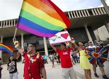 Same sex marriage supporters Lance Namihara (L), Calvin Marquez (C) and Aleeciya Parker rally at the Hawaii State Capital as the State Legislature convenes for the third and final vote on allowing same sex marriage to be legal in the state of Hawaii in Honolulu, November 8, 2013. REUTERS/Hugh Gentry