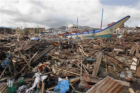 A fishing boat which slammed into damaged houses lie atop debris after super Typhoon Haiyan battered Tacloban city, central Philippines November 10, 2013. REUTERS/Romeo Ranoco