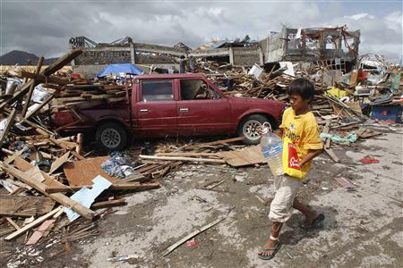 A boy carrying a plastic bottle of water walks past a car which slammed into damaged houses after super Typhoon Haiyan battered Tacloban city, central Philippines November 10, 2013. REUTERS/Romeo Ranoco