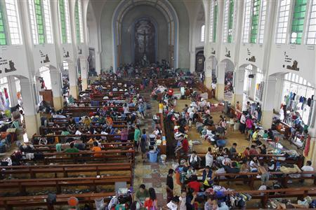 Residents seek refuge inside a Catholic church which has been converted into an evacuation center after super Typhoon Haiyan battered Tacloban city, central Philippines November 10, 2013. REUTERS/Romeo Ranoco