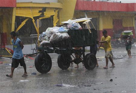Residents use a cart to transport their belongings after super Typhoon Haiyan battered Tacloban city, central Philippines November 10, 2013. REUTERS/Romeo Ranoco