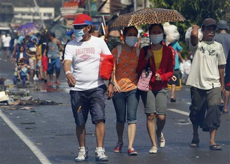 Survivors wearing face masks walk downtown after super Typhoon Haiyan battered Tacloban city, central Philippines November 10, 2013. REUTERS/Romeo Ranoco