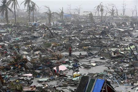 People stand among debris and ruins of houses destroyed after Super Typhoon Haiyan battered Tacloban city in central Philippines November 10, 2013. REUTERS/Erik De Castro