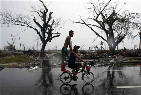 Residents ride a bicycle past a road lined with debris after Super Typhoon Haiyan battered Tacloban city in central Philippines November 10, 2013. REUTERS/Erik De Castro