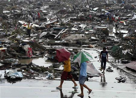 Residents walk past the ruins of houses, which were destroyed after Super Typhoon Haiyan battered Tacloban city in central Philippines November 10, 2013. REUTERS/Erik De Castro