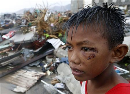 A boy who was wounded by flying debris due to Super Typhoon Haiyan stays at the ruins of his family's house in Tacloban city November 10, 2013. REUTERS/Erik De Castro