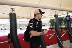 Lotus F1 Formula One driver Kimi Raikkonen of Finland walks through turnstiles before the third practice session of the Abu Dhabi F1 Grand Prix at the Yas Marina circuit on Yas Island, November 2, 2013. REUTERS/Caren Firouz
