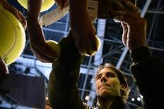 Rafael Nadal of Spain signs autographs after defeating Roger Federer of Switzerland in their men's singles semi-final tennis match at the ATP World Tour Finals at the O2 Arena in London November 10, 2013. REUTERS/Dylan Martinez