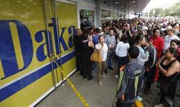 """Compradores esperan fuera de una tienda Daka para comprar artículos electrónicos en Caracas. REUTERS/Carlos Garcia Rawlins. El Gobierno de Venezuela anunció el domingo la detención de cinco gerentes de tiendas como parte de lo que ha calificado como una """"guerra económica"""" entre el Estado socialista e """"inescrupulosos"""" empresarios."""