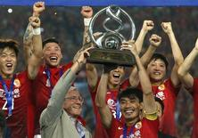 China's Guangzhou Evergrande coach Marcello Lippi (front L) and player Zheng Zhi (front R) hold up the trophy after winning their final match of the AFC Champions' League against South Korea's FC Seoul at Tianhe stadium in the southern Chinese city of Guangzhou November 9, 2013. REUTERS/Bobby Yip