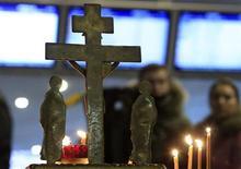Люди участвуют в траурном молебне на месте смертносного взрыва в московском аэропорту Домодедово 26 января 2011 года. Суд в понедельник приговорил к пожизненному заключению троих и к 10 годам тюрьмы - одного из соучастников боевика, около трех лет назад подорвавшего себя в московском аэропорту Домодедово, в результате чего погибли 37 человек. REUTERS/Sergei Karpukhin