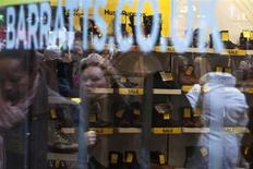 Passers-by are reflected in the display window of Barratts shoe shop on Oxford Street in central London, December 8, 2011. REUTERS/Finbarr O'Reilly