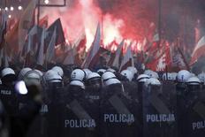 Полицейские берут в оцепление здание российского посольства во время марша в День независимости в Варшаве 11 ноября 2013 года. Польские полицейские применили в понедельник резиновые пули для разгона одетых в маски молодых людей, использовавших пиротехнику и поджигавших автомобили во время марша националистов в центре Варшавы. REUTERS/Kacper Pempel
