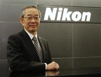 Nikon Corp's President Makoto Kimura poses in front of the company logo before an interview with Reuters in Tokyo November 12, 2013. Japan's iconic camera maker Nikon Corp will rely on emerging market consumer sales to fuel growth even though it forecast in August its first-ever drop in digital SLR sales, Kimura told Reuters. Kimura said on Tuesday Nikon is counting on consumers in markets like Brazil and India to drive sales of its single-lens reflex cameras (SLRs) in the mid-term and has no immediate plans to follow its rivals into other sectors. REUTERS/Toru Hanai