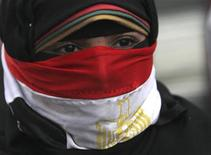 A woman, with the national flag covering part of her face, takes part in a protest rally against then Egyptian President Mohamed Mursi and members of the Muslim Brotherhood in front of the courthouse and the Attorney General's office, near Tahrir Square in Cairo, in this March 8, 2013 file picture. REUTERS/Amr Abdallah Dalsh/Files