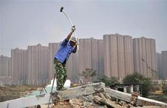 A worker wields a hammer at a demolition site in front of new residential buildings in Hefei, Anhui province, October 19, 2013. REUTERS/Stringer