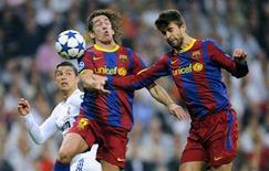 Jogador do Real Madrid Cristiano Ronaldo disputa a bola com Carles Puyol e Gerard Piqué durante partida pela semifinal da Liga dos Campeões da Europa, no estágio Santiago Bernabéu, em Madri. 27/04/2011. REUTERS/Felix Ordonez