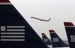 US Airways et American Airlines ont accepté de renoncer à plusieurs dizaines de créneaux de décollage et d'atterrissage pour obtenir le feu vert des autorités à leur projet de fusion. L'accord va donner naissance à la première compagnie aérienne mondiale. /Photo prise le 12 novembre 2013/REUTERS/Larry Downing