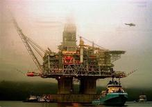 The Hibernia offshore oil production rig prepares to be towed, in the predawn fog, from its construction berth in Trinity Bay, Newfoundland, to the oil fields 300 kilometers from St. John's in the North Atlantic. The Hibernia rig is the largest in the world and its concrete base will rest on the ocean floor.