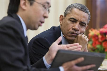 U.S. President Barack Obama watches as Todd Park (L), Assistant to the President and Chief Technology Officer, shows him information on a tablet during a meeting in the Oval Office, in this April 15, 2013 handout photograph obtained on October 24, 2013. REUTERS/Pete Souza/The White House/Handout