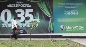 Женщина проходит мимо рекламного плаката Мегафона в Ставрополе 14 мая 2013 года. Второй по величине российский мобильный оператор Мегафон увеличил чистую прибыль в третьем квартале на 2,9 процента в годовом выражении, что совпало с прогнозом аналитиков, опрошенных Рейтер. REUTERS/Eduard Korniyenko