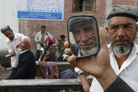 An ethnic Uighur man checks a mirror after getting his beard shaved by a barber (R) on a street in Aksu, Xinjiang Uighur Autonomous Region July 21, 2013. REUTERS/William Hong/Files