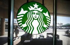 A Starbucks logo hangs on a window at a newly designed Starbucks coffee shop in Fountain Valley, California August 22, 2013. REUTERS/Mike Blake