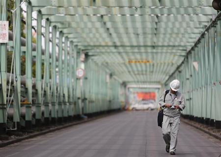 A man walks inside a factory at Keihin industrial zone in Kawasaki, south of Tokyo June 28, 2013. REUTERS/Yuya Shino