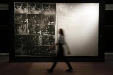 """Сотрудница Sotheby's проходит мимо картины """"Авария серебряной машины"""" Энди Уорхола в Лондоне 11 октября 2013 года. Щедрость коллекционеров произведений искусства позволила Sotheby's провести крупнейший за свою историю аукцион, где лидером продаж оказалась работа Энди Уорхола, купленная за рекордные для художника $105 миллионов. REUTERS/Stefan Wermuth"""