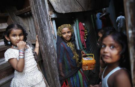 Girls react to the camera as they play in an alley at a slum in Mumbai October 28 , 2013. REUTERS/Danish Siddiqui