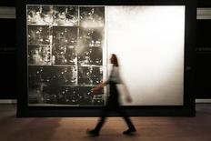 """A Sotheby's employee poses with Andy Warhol's artwork """"Silver Car Crash"""" at Sotheby's auction house in London in this October 11, 2013 handout photo. The artwork, initially valued at $60 million, sold at auction at Sotheby's in New York November 13, 2013 for $105,445,000. REUTERS/Stefan Wermuth/Files"""