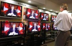 An electronics store employee watches Canada's Prime Minister Stephen Harper deliver a national televised address in Calgary, Alberta, December 3, 2008. REUTERS/Todd Korol