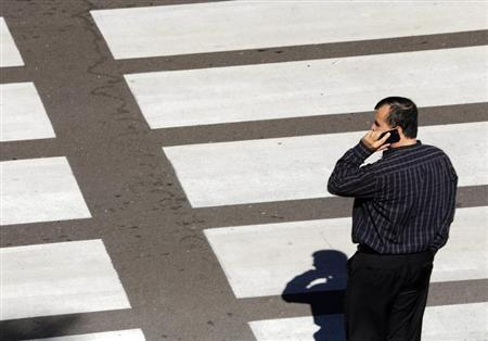 A man talks on his mobile phone as he waits at a crosswalk at Lindbergh Field Airport in San Diego, California, November 6, 2013. REUTERS/Mike Blake